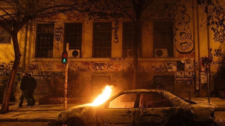 A fire burns a car during clashes in the Athens neighborhood of Exarchia, a haven for extreme leftists and anarchists late Thursday, Feb. 26, 2015. The minor clashes broke out after an anti-government protest against Greece's four-month bailout extension agreement with European Union. (AP Photo)