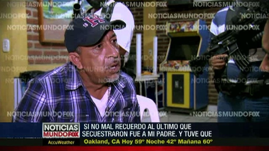 "In this frame grab from a Dec. 2013 file video interview by Mundo Fox via APTN, shows Servando ""La Tuta"" Gomez,"" leader of the Knights Templar cartel, giving an interview as masked and armed men watch in an unknown location in Mexico's Michoacan state. Gomez, one of Mexico's most-wanted drug lords, was captured early Friday, Feb. 27, 2015 by federal police in the capital city of Morelia, according to a Mexican official. Watermarks on the video were added by Mundo Fox. (AP Photo/Mundo Fox via APTN, File)"