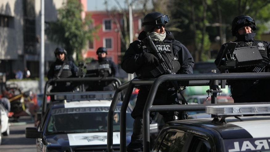 "Federal police patrol as part of increased security outside the SEIDO, the organized-crime division of Mexico's Attorney General Office where high profile detainees are sometimes shown to the press in Mexico City, Friday, Feb. 27, 2015. The leader of the Knights Templar cartel Servando ""La Tuta"" Gomez,"" one of Mexico's most-wanted drug lords, was captured early Friday by federal police in the capital city of Morelia, according to a Mexican official. It could not be confirmed if Gomez was inside the SEIDO building. (AP Photo/Marco Ugarte)"