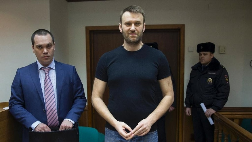 Russian opposition activist Alexei Navalny, center, and his lawyer, left, stand in a court room in Moscow, Russia, Friday, Feb. 27, 2015. Navalny was detained earlier this month for 15 days for distributing leaflets for an anti-government march, which he will miss if he remains in prison. (AP Photo/Pavel Golovkin)