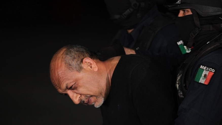 "Federal police escort who they identify as Servando ""La Tuta"" Gomez,"" leader of the Knights Templar cartel, to a waiting helicopter at a Federal hanger in Mexico City, Friday, Feb. 27, 2015. Gomez, a former school teacher who became one of Mexico's most-wanted drug lords as head of the Knights Templar cartel, was captured early Friday by federal police, according to Mexican officials. (AP Photo/Marco Ugarte)"