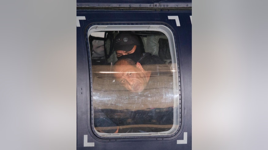 "Servando ""La Tuta"" Gomez,"" leader of the Knights Templar cartel, looks out the window of a Federal police helicopter at the Attorney General's Office hangar in Mexico City, Friday, Feb. 27, 2015. Gomez, a former school teacher who became one of Mexico's most-wanted drug lords as head of the Knights Templar cartel, was captured early Friday by federal police, according to Mexican officials. (AP Photo/Rebecca Blackwell)"