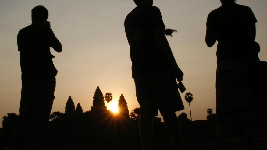 FILE - In this March 30, 2008, file photo, tourists talk as they wait to take pictures of sunrise in front of the famed Angkor Wat temple in Siem Reap province in northwestern Cambodia. Cambodia's most popular tourist attraction, the complex of ancient temples that includes Angkor Wat, is suffering from a form of overexposure as at least five foreign visitors have been arrested and deported this year for taking nude photos at the sacred sites.(AP Photo/Heng Sinith)