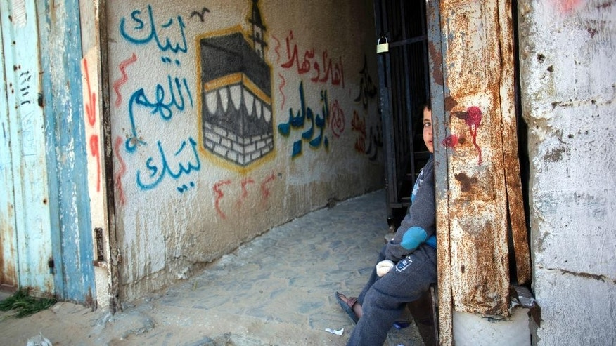 Feb. 27, 2015 - A Palestinian boy sits next to an old wall mural depicting the Kaaba, Islam's holiest site and a center point of the annual Hajj pilgrimage, in the Rafah refugee camp, southern Gaza Strip. Thousands of people have been shut out of a Muslim pilgrimage to Saudi Arabia because they cannot leave the sealed territory to travel to Mecca, Saudi Arabia, for the minor umrah pilgrimage.