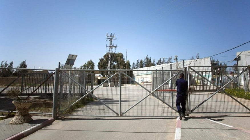 A Palestinian Hamas police officer stands next to the last gate of the Palestinian side of the border with Egypt in the southern Gaza Strip, Friday, Feb. 27, 2015. With the war-battered Gaza Strip's borders closed, thousands of people have been shut out of a Muslim pilgrimage to Saudi Arabia because they cannot leave the sealed territory. Some 7,500 Gazans have sought to travel to Mecca, Saudi Arabia, for the minor umrah pilgrimage but have been turned away because Egypt restricts movement in and out of the coastal enclave.(AP Photo/Khalil Hamra)