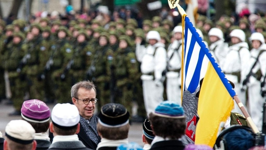 CAPTION CORRECTION, CORRECTS CITY IN CAPTION AND IPTC FIELD - Estonian President Toomas Hendrik Ilves greets people in Narva, Estonia, Tuesday, Feb. 24, 2014. Troops and vehicles from U.S. and NATO regiments took part in the military parade to mark Estonia's Independence Day near the Russian border, in the first known official appearance of the forces so close to the former Cold War enemy. (AP Photo/Liis Treimann)
