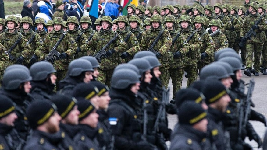 CAPTION CORRECTION, CORRECTS CITY AND DATE - Estonian troops parade in Narva, Estonia, Tuesday, Feb. 24, 2015. Troops and vehicles from U.S. and NATO regiments took part in the military parade to mark Estonia's Independence Day near the Russian border, in the first known official appearance of the forces so close to the former Cold War enemy. (AP Photo/Liis Treimann)