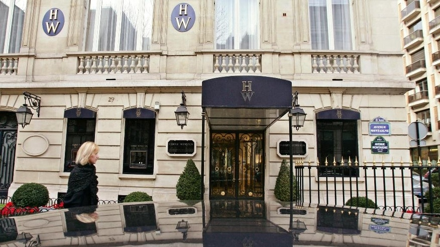 FILE - This Friday Dec. 5, 2008 file photo shows the entrance of the Harry Winston jewelry store near the Champs-Elysees in Paris. Eight people have been convicted in connection with a spectacular 2008 holdup at a Harry Winston jewelry shop in Paris, in which three cross-dressing gunmen stole about $92 million in loot, a defense lawyer said Saturday Feb. 28, 2015. In the robbery, the gunmen wore silky wigs, skirts, stockings and high heels, and took less than 20 minutes to steal hundreds of jewelry pieces and watches. (AP Photo/Francois Mori, file)