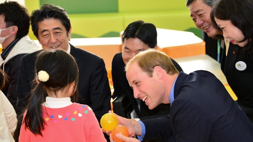 Britain's Prince William, right, and Japanese Prime Minister Shinzo Abe, left, play with children as they visit Smile Kids Park playground in Motomiya city, Japan's northeastern prefecture of Fukushima, Saturday, Feb. 28, 2015.  Among the highlights of William's trip, through Sunday, is a visit to the school in the northeastern region of Fukushima, where some areas have been closed off around a nuclear power plant that went into multiple meltdowns four years ago.(AP Photo/Japan Pool) JAPAN OUT
