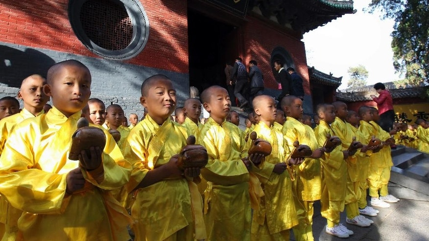 In this Oct. 22, 2012 photo, visitors walk past as young monks offer prayers outside the Shaolin Temple in Dengfeng city in central China's Henan province. The temple which is historically known for its martial arts traditions but recently has gained a controversial reputation for aggressive commercialization is planning to build a $297-million complex that includes a temple, a hotel, a kung fu academy and a golf course in Australia. (AP Photo) CHINA OUT