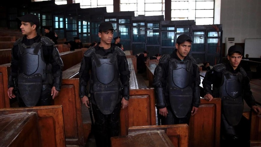 Egyptian policemen stand guard in front of the courtroom defendant's cage during a verdict hearing on a case that stems from clashes near the Muslim Brotherhood's headquarters on June 30, 2013, four days before the ouster of Islamist President Mohammed Morsi, that left 11 people dead and 91 wounded, in Cairo, Egypt, Saturday, Feb. 28, 2015. The Egyptian court sentenced four members of the banned Muslim Brotherhood organization to death and 14 to life in prison. Some 22,000 people have been arrested since Morsi's ouster, including most of the Brotherhood's leaders, as well as non-Islamist activists swept up by police during protests. (AP Photo/Hassan Ammar)