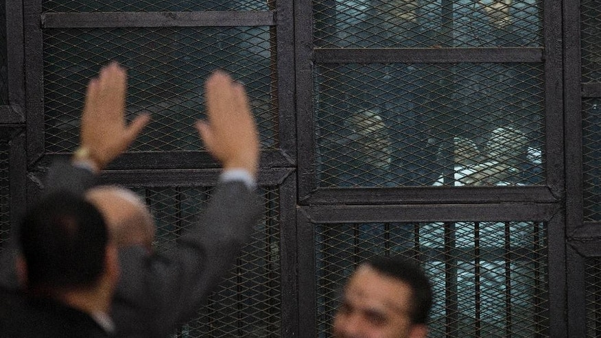 An Egyptian lawyer greets Muslim Brotherhood Supreme Guide Mohammed Badie, center, as he appears in a courtroom cage in Cairo, Egypt, Saturday, Feb. 28, 2015. The Egyptian court sentenced four members of the banned Muslim Brotherhood organization to death and 14 to life in prison on Saturday. Badie and his deputy Khairat al-Shater were among those sentenced to life, along with former lawmaker Mohammed el-Beltagy and party head Saad el-Katatni and his deputy, Essam el-Erian. The men were accused of murder and possession of firearms, among other charges. The verdicts can be appealed. (AP Photo/Hassan Ammar)