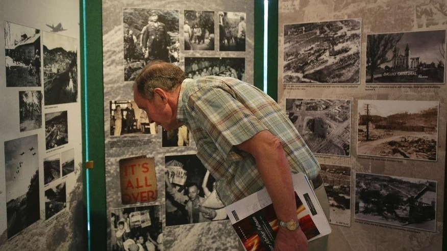In this Feb. 3, 2015 photo, a visitor looks at photos at a commemorative event for the 70th year of the Battle for Manila at the Ayala Museum in suburban Makati, south of Manila, Philippines. Seventy years have not dulled the memories of survivors of the month-long Battle of Manila. The mass killings by Japanese forces, the loved ones lost and the desperation are etched in their minds, as is the elation when American forces finally rescued them in the closing months of World War II. (AP Photo/Aaron Favila)