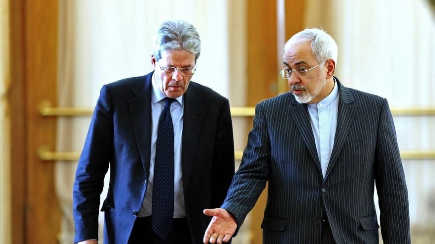 Iranian Foreign Minister Mohammad Javad Zarif, right, speaks with his Italian counterpart Paolo Gentiloni as they arrive to give a joint press conference in Tehran, Iran, Saturday, Feb. 28, 2015.  Zarif said the world should not allow the hard-line Israeli leader to undermine peace. He was referring to Netanyahu's planned speech at the U.S. Congress next week on the emerging nuclear deal that he considers dangerous. (AP Photo/Ebrahim Noroozi)