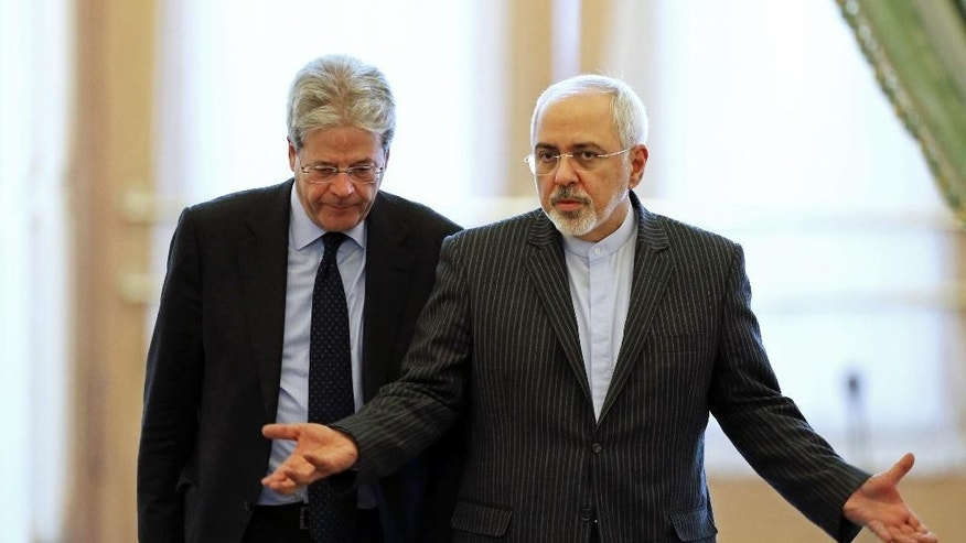 Iranian Foreign Minister Mohammad Javad Zarif, right, speaks with his Italian counterpart Paolo Gentiloni as they arrive to attend a joint press conference in Tehran, Iran, Saturday, Feb. 28, 2015. Zarif says the world should not allow the hard-line Israeli leader to undermine peace. He was referring to Netanyahu's planned speech at the U.S. Congress next week on the emerging nuclear deal that Netanyahu considers dangerous. (AP Photo/Ebrahim Noroozi)