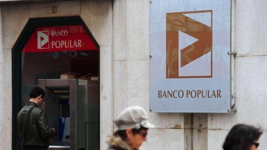 LISBON, PORTUGAL - MARCH 29:  A man stands behind a cash machine of the Banco Popular on March 29, 2011 in Lisbon, Portugal. The pressure continues on Portugal's weak economy to accept a bailout - estimated to be as high as 80 Million Euros - after last week's resignation of Prime Minister Jose Socrates.  (Photo by Jasper Juinen/Getty Images)