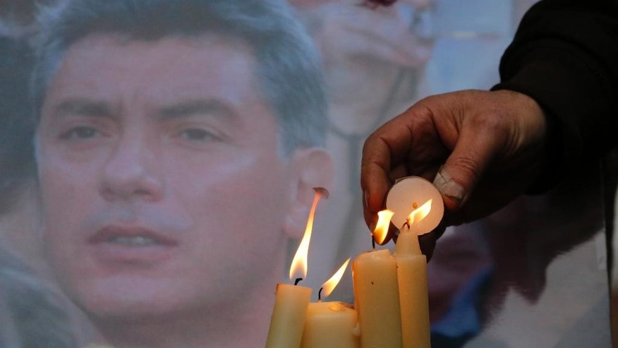 People light candles in memory of Boris Nemtsov, seen behind, at the monument of political prisoners 'Solovetsky Stone' in central St.Petersburg, Russia, Saturday, Feb. 28, 2015. Nemtsov was gunned down Saturday near the Kremlin, just a day before a planned protest against the government. (AP Photo/Dmitry Lovetsky)