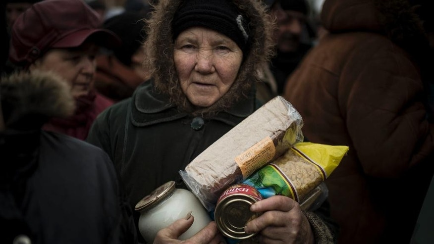 A local elderly woman holds humanitarian aid distributed in Popasna, eastern Ukraine, Saturday, Feb. 28, 2015.  The recent pullback of some weapons from the line separating government and rebel forces in Ukraine seems to have boosted the prospects for peace, although both sides are warning of their readiness to resume fighting if necessary. (AP Photo/Evgeniy Maloletka)