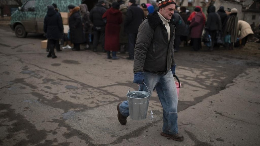 A man carries buckets with water as local residents queue to get humanitarian aid being distributed in Popasna, eastern Ukraine, Saturday, Feb. 28, 2015. The recent pullback of some weapons from the line separating government and rebel forces in Ukraine seems to have boosted the prospects for peace, although both sides are warning of their readiness to resume fighting if necessary.  (AP Photo/Evgeniy Maloletka)