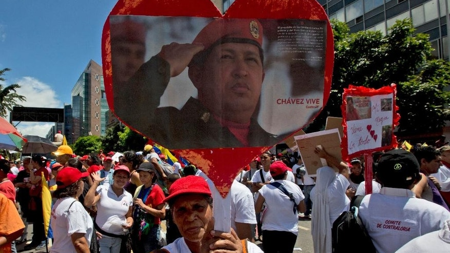 "A supporter of Venezuela's President Nicolas Maduro holdups a picture of the late President Hugo Chavez during a march to commemorate the anniversary of a convulsion of violence in Caracas known as the ""Caracazo"", in Caracas, Venezuela, Saturday, Feb. 28, 2015. Marchers are taking to the streets of Caracas in dueling protests, with one group calling attention to a crackdown on opponents of the government and another showing support for the embattled socialist administration. (AP Photo/Fernando Llano)"
