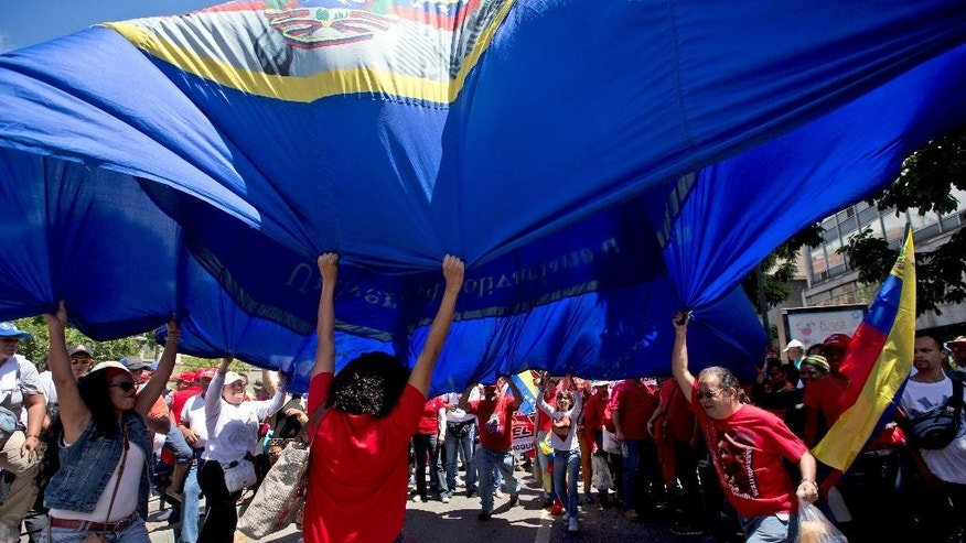 "Supporters of Venezuela's President Nicolas Maduro waves a flag with the image of Venezuelan hero Simon Bolivar during a march to commemorate the anniversary of a convulsion of violence in Caracas known as the ""Caracazo"", in Caracas, Venezuela, Saturday, Feb. 28, 2015. Marchers are taking to the streets of Caracas in dueling protests, with one group calling attention to a crackdown on opponents of the government and another showing support for the embattled socialist administration. (AP Photo/Fernando Llano)"