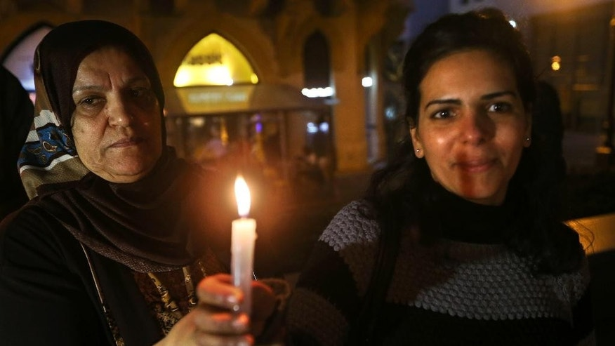 Palestinian women hold candles during a vigil held by a Palestinian group in solidarity with Christians abducted in Syria and Iraq, in downtown Beirut, Lebanon Sunday, March 1, 2015. The Islamic State group, which has repeatedly targeted religious minorities in Syria and Iraq, abducted more than 220 Assyrians this week in northeastern Syria. (AP Photo/Hussein Malla)