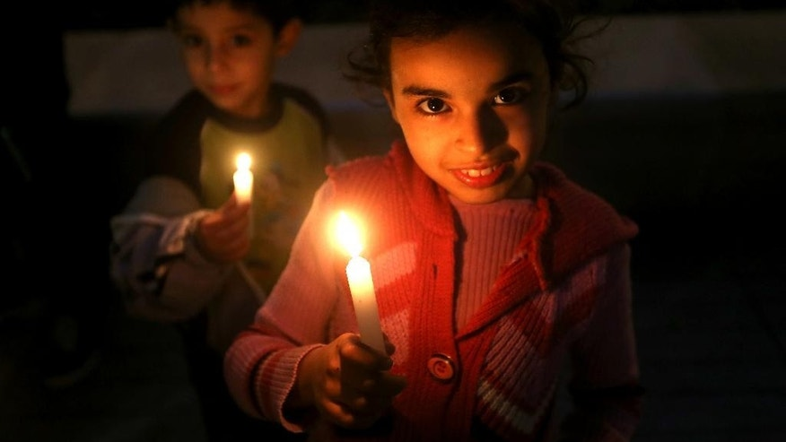 Palestinian children hold candles during a vigil held by a Palestinian group in solidarity with Christians abducted in Syria and Iraq, in downtown Beirut, Lebanon Sunday, March 1, 2015. The Islamic State group, which has repeatedly targeted religious minorities in Syria and Iraq, abducted more than 220 Assyrians in the past week in northeastern Syria. (AP Photo/Hussein Malla)