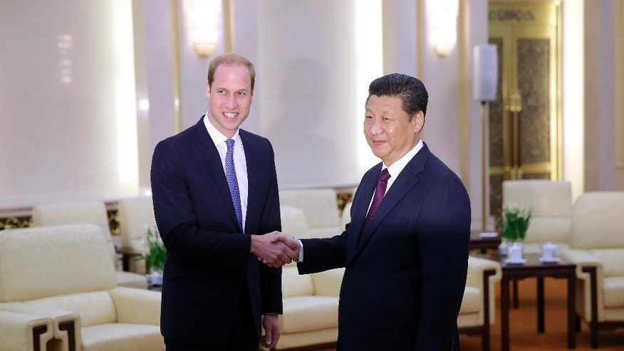 Britain's Prince William, left, meets Chinese President Xi Jinping at the Great Hall of the People in Beijing Monday, March 2, 2015. William is making the first official visit to mainland China by a senior British royal in a generation, testing his diplomatic mettle as the second in line to the throne. (AP Photo/Feng Li, Pool)