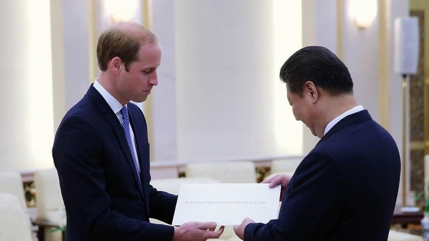 Britain's Prince William, left, gives a letter from Queen Elizabeth to Chinese President Xi Jinping at the Great Hall of the People in Beijing Monday, March 2, 2015. William is making the first official visit to mainland China by a senior British royal in a generation, testing his diplomatic mettle as the second in line to the throne. (AP Photo/Feng Li, Pool)