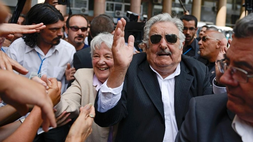 Uruguay's former President Jose Mujica and wife Lucia Topolansky greet supporters after the swearing-in ceremony for Uruguay's new President Tabare Vazquez at Independence Plaza in Montevideo, Uruguay, Sunday, March 1, 2015. Mujica, who still lives on a flower farm with his wife, rarely dons a tie and drives an old VW Beetle, has led Uruguay through stable economic growth and better wages. His social agenda has included laws approving gay marriage and the creation of the world's first national marketplace for legal marijuana. (AP Photo/Matilde Campodonico)