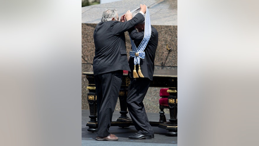 Uruguay's new President Tabare Vazquez, right, receives the presidential sash from Uruguay's outgoing President Jose Mujica during a ceremony at Independence Plaza in Montevideo, Uruguay, Sunday, March 1, 2015. (AP Photo/Natacha Pisarenko)