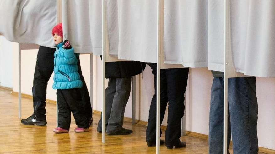 A little girl looks out of a voting booth at a polling station in Tallinn, Estonia, on Sunday, March 1, 2015. Estonians are voting for a new Parliament in an election dominated by economic issues and security concerns due to tension in Ukraine. (AP Photo/Liis Treimann)