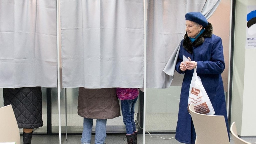 A woman leaves a voting booth at a polling station in Tallinn, Estonia, on Sunday, March 1, 2015. Estonians are voting for a new Parliament in an election dominated by economic issues and security concerns due to tension in Ukraine. (AP Photo/Liis Treimann)