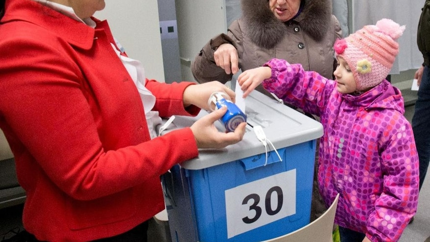 A little girl helps her mother to cast a ballot at a polling station in Tallinn, Estonia, on Sunday, March 1, 2015. Estonians are voting for a new Parliament in an election dominated by economic issues and security concerns due to tension in Ukraine. (AP Photo/Liis Treimann)