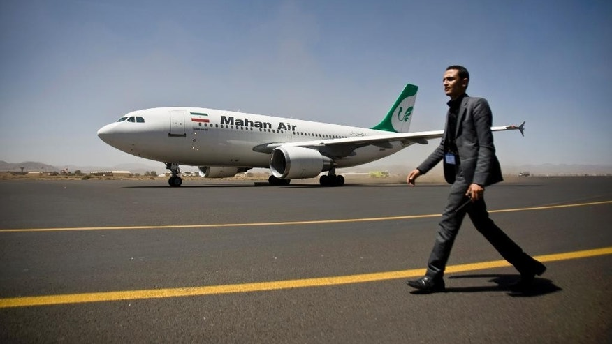 A Yemeni airport security official walks on the tarmac next to a plane from the Iranian private airline Mahan Air at the international airport in Sanaa, Yemen, Sunday, March 1, 2015. The first direct flight from Iran to the rebel-held Yemeni capital arrived, Sunday, an Airbus 310 carrying Iranians including aid workers from the Iranian Red Crescent as Yemen's Shiite rebels formalize ties with the regional Shiite powerhouse. The rebels, who overran the capital, Sanaa, last September, are widely believed to have support from Iran, a claim they frequently denied. (AP Photo/Hani Mohammed)