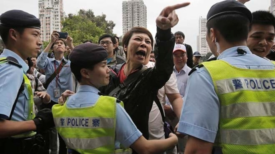 March 1, 2015: A local villager, center, gestures at protesters demonstrating against mainland Chinese shoppers at a suburban district of Yuen Long in Hong Kong. The protest erupted into chaos as police used pepper spray to break up scuffles between protesters and  local villagers.