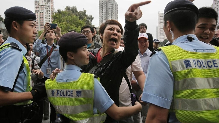 A local villager, center, gestures at protesters demonstrating against mainland Chinese shoppers at a suburban district of Yuen Long in Hong Kong, Sunday, March 1, 2015. The protest erupted into chaos as police used pepper spray to break up scuffles between protesters and  local villagers. demonstration and was the latest to target the influx of mainland shoppers to Hong Kong, where many blame their voracious buying habits for distorting the local economy. (AP Photo/Vincent Yu)