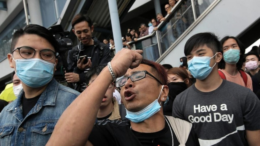 Protesters demonstrating against mainland Chinese shoppers gesture against local villagers at a suburban district of Yuen Long in Hong Kong, Sunday, March 1, 2015. Hong Kong police have used pepper spray to break up scuffles between protesters demonstrating against mainland Chinese shoppers and villagers from a border town. Sunday's unruly demonstration was the latest to target the influx of mainland shoppers to Hong Kong, where many blame their voracious buying habits for distorting the local economy. (AP Photo/Vincent Yu)