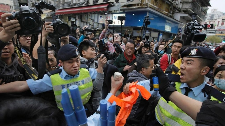 Police officers try to control the confrontation between activists demonstrating against mainland Chinese shoppers and local villagers at a suburban district of Yuen Long in Hong Kong, Sunday, March 1, 2015. Hong Kong police have used pepper spray to break up scuffles between protesters demonstrating against mainland Chinese shoppers and villagers from a border town. Sunday's unruly demonstration was the latest to target the influx of mainland shoppers to Hong Kong, where many blame their voracious buying habits for distorting the local economy. (AP Photo/Vincent Yu)