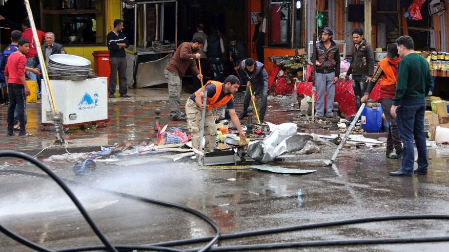 Feb. 7, 2015: Iraqis clean up the site of a suicide bombing that targeted a street filled with hardware stores, killing over 20 people and wounding at least 45, in the Iraqi capital's southeastern neighborhood of New Baghdad.