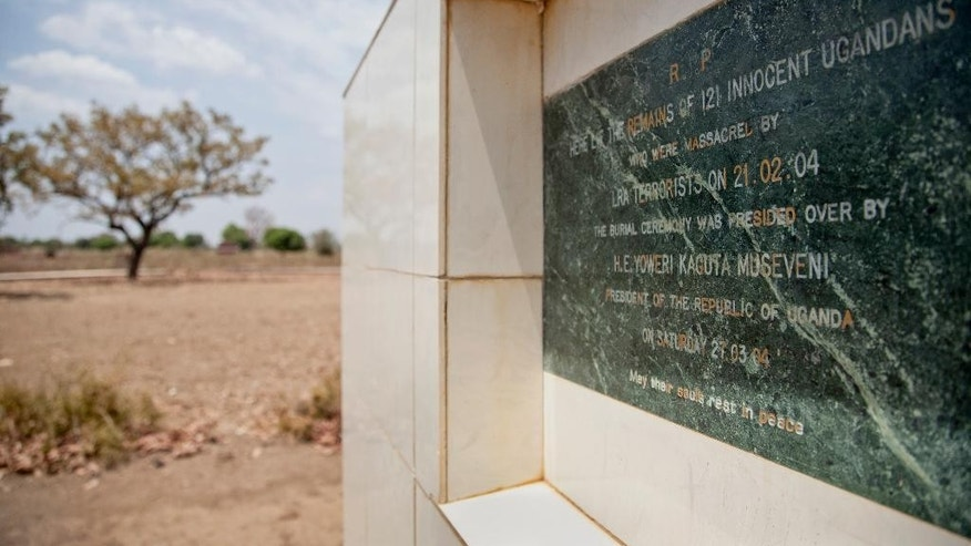 In this photo taken Thursday, Feb. 12, 2015, a memorial marks the location of a mass burial site of those massacred in 2004 by the Lord's Resistance Army (LRA), at the Barlonyo displaced persons camp in northern Uganda. Eleven years after the LRA attacked Barlonyo, the International Criminal Court in The Hague is preparing to try senior LRA commander Dominic Ongwen for war crimes and crimes against humanity and while Ugandan military officials and survivors say he helped direct the attack on the camp in Barlonyo, some survivors of the Feb. 21, 2004, attack say Ongwen should not be tried by the ICC. (AP Photo/Rebecca Vassie)