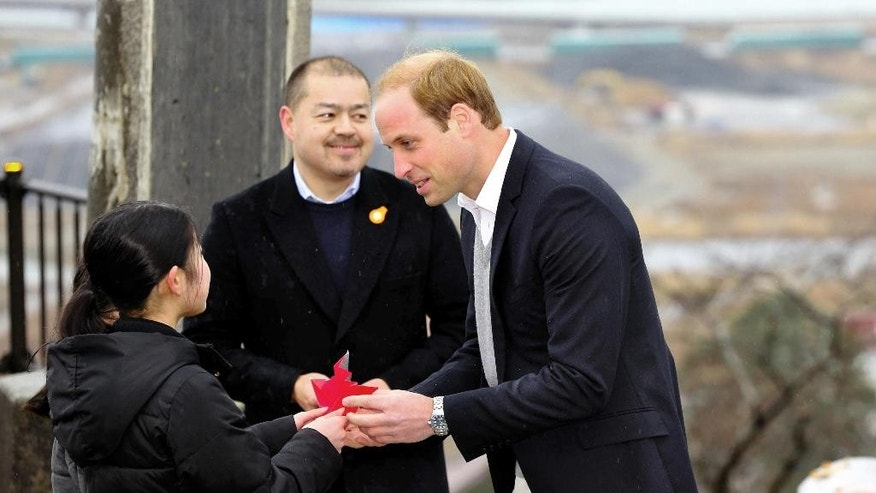 Britain's Prince William, right, receives paper crane from girls as he visits the ravaged waterfront area devastated by the 2011 tsunami at Hiyoriyama Park in Ishinomaki, Miyagi Prefecutre, northeastern Japan, Sunday, March 1, 2015. (AP Photo/Kyodo News) JAPAN OUT, MANDATORY CREDIT