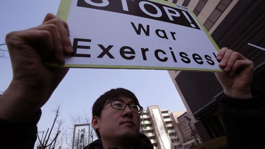 "A protester holds a sign to denounce the annual joint military exercises, dubbed Key Resolve and Foal Eagle, between South Korea and the United States, during a rally near U.S. Embassy in Seoul, South Korea, Monday, March 2, 2015. North Korea on Monday fired two short-range ballistic missiles into the sea and warned of ""merciless strikes"" against its enemies as allies Seoul and Washington launched annual military drills Pyongyang claims are preparation for a northward invasion. (AP Photo/Lee Jin-man)"