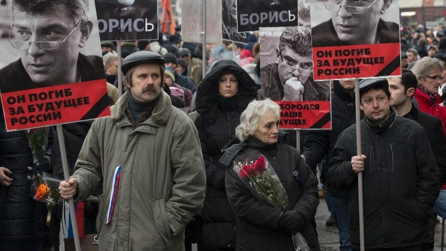 March 1, 2015: People carry portraits of opposition leader Boris Nemtsov, who was gunned down on Friday, Feb. 27, 2015 near the Kremlin, with words reading 'he died for the future of Russia!' in Moscow, Russia. (AP)