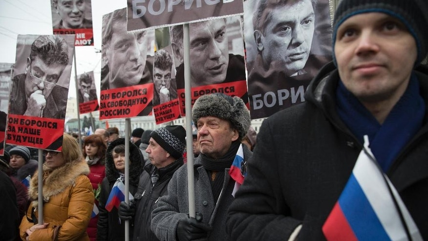 March 1, 2015: People carry portraits of opposition leader Boris Nemtsov who was gunned down on Friday, Feb. 27, 2015 near the Kremlin, with words reading 'He fought for a free of Russia, He fought for our future!' in Moscow, Russia. (AP)