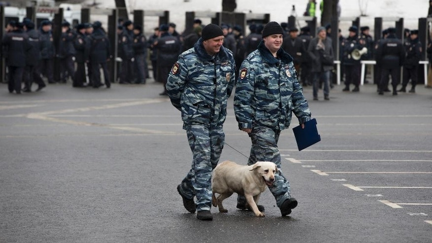 March 1, 2015: Police officers walk with their sniffing dog checking the area prior a march in memory of opposition leader Boris Nemtsov, who was gunned down on Friday, Feb. 27, 2015 near the Kremlin, in Moscow, Russia. (AP)