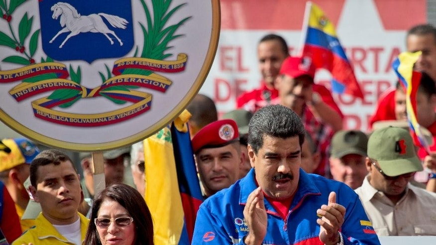 Venezuela's President Nicolas Maduro, right, and his wife Cilia Flores greet supporters during a rally outside of Miraflores presidential palace in Caracas, Venezuela, Saturday, Feb. 28, 2015. Venezuelans took to the streets of Caracas in dueling demonstrations on Saturday, with one group calling attention to a crackdown on opponents of the government and another showing support for the embattled socialist administration. T (AP Photo/Fernando Llano)