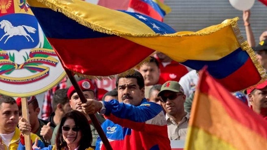 Feb. 28, 2015: Venezuela's President Nicolas Maduro, center, waves a national flag during a rally in Caracas, Venezuela. (AP)