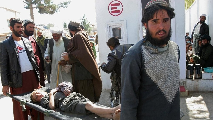 In this Thursday, Feb. 26, 2015 photo, Afghans carry an injured boy at an emergency hospital in Helmand province, south of Kabul, Afghanistan. The Afghan army is waging its largest-ever solo offensive against the Taliban, hoping to strike a decisive blow ahead of the spring fighting season and prove it can route the insurgents without the aid of U.S. and NATO combat troops. Afghan President Ashraf Ghani heads to Washington later in March, 2015, where he is expected to seek enhanced U.S. military backup, particularly air support. (AP Photo/Abdul Khaliq)