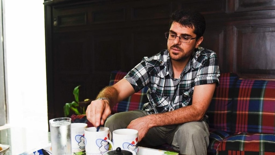 In this Feb. 24, 2015 photo, Omar Abdelahdi Faraj, from Syria, adds sugar to a cup of coffee during an interview inside the home he shares with five other former Guantanamo detainees in Montevideo, Uruguay. Faraj, 34, said he and his housemates want to work, but that first they needed to address health problems, from anxiety and an inability to concentrate to physical ailments like stomach bacterial problems and blurred vision. (AP Photo/Matilde Campodonico)